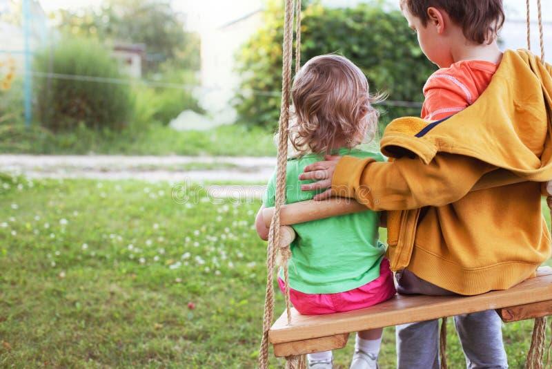 Kinderen die op een schommeling in de tuin zitten stock fotografie