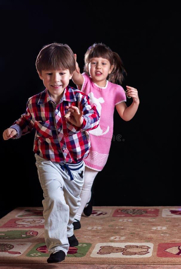 Kinderen die op een zwarte achtergrond spelen royalty-vrije stock afbeelding