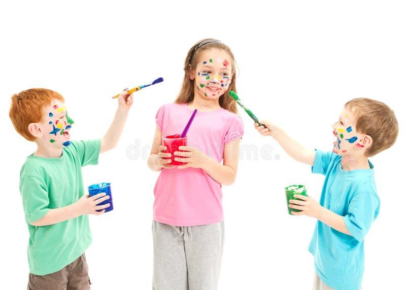 Kinderen die op elkaar schilderen royalty-vrije stock afbeeldingen