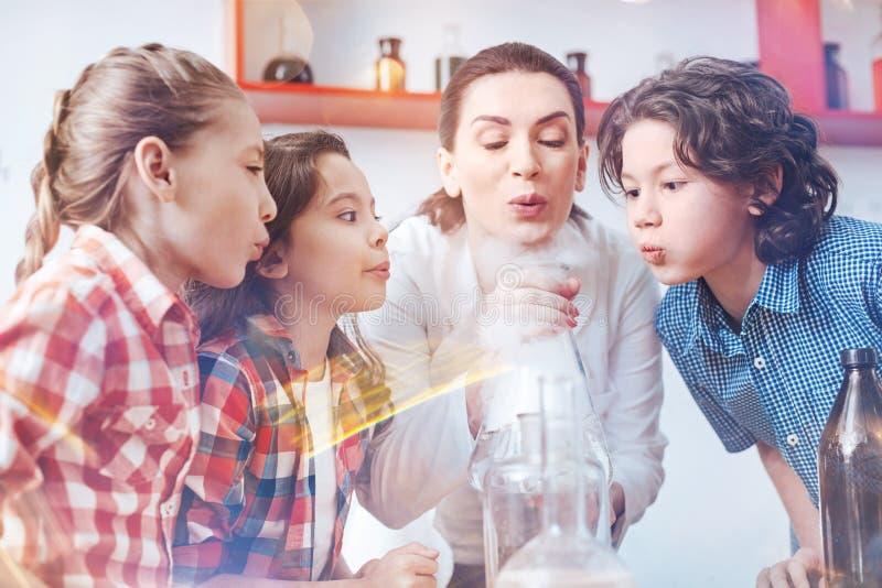 Kinderen die op fuming laboratoriumfles op school blazen royalty-vrije stock foto