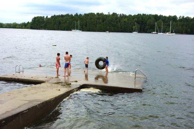 Kinderen die op het meer spelen stock afbeelding