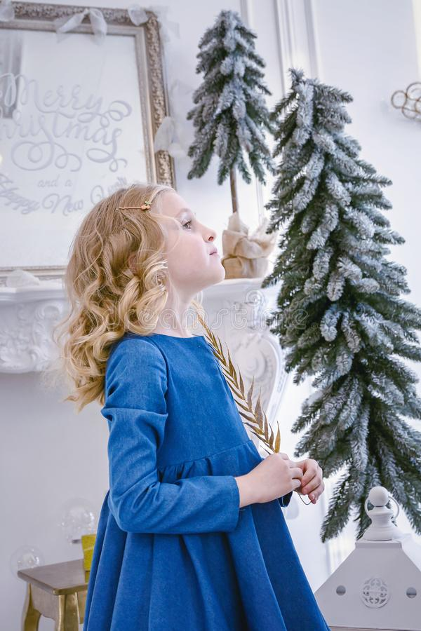 Kinderen die op het Nieuwjaar en Kerstmis wachten Leuk meisje met een gouden tak in haar handendromen van giften stock fotografie