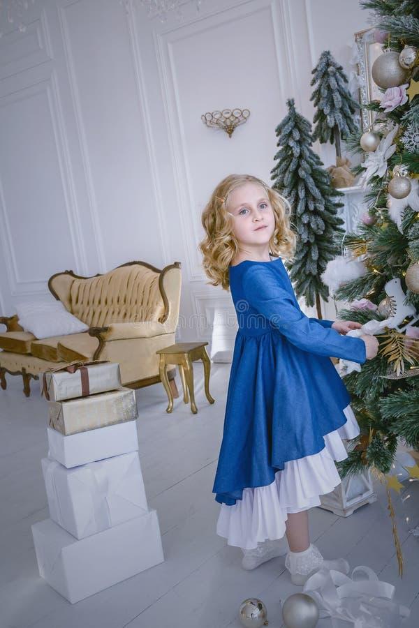 Kinderen die op het Nieuwjaar en Kerstmis wachten Meisje die Kerstboom thuis verfraaien door snuisterijen royalty-vrije stock foto