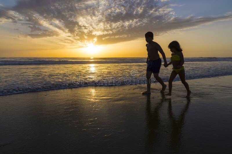 Kinderen die op het strand bij schemer baden royalty-vrije stock foto's