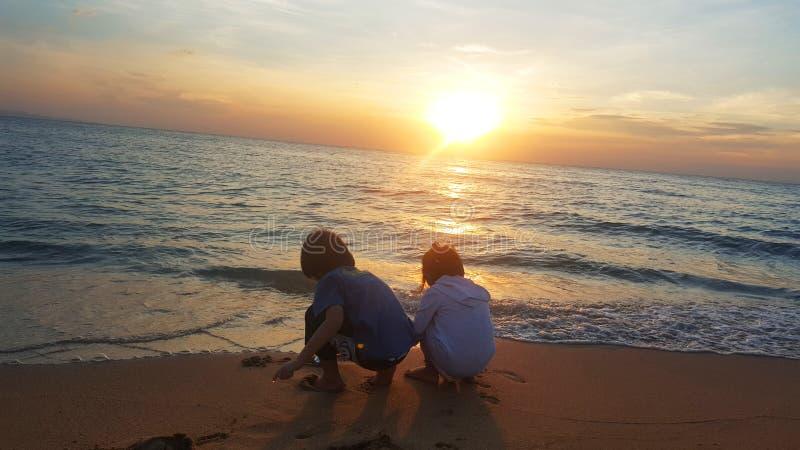 Kinderen die op het strand bij zonsondergang spelen overzees, Reis en vakantieconcept, het concept van de de Zomertijd stock afbeeldingen