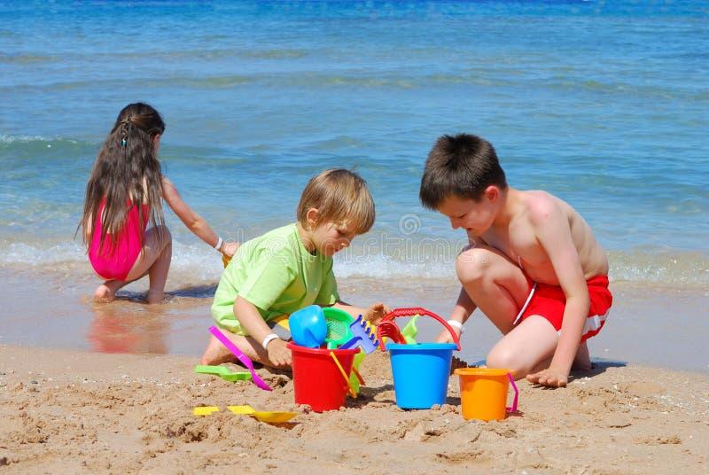 kinderen die op het strand spelen stock foto's