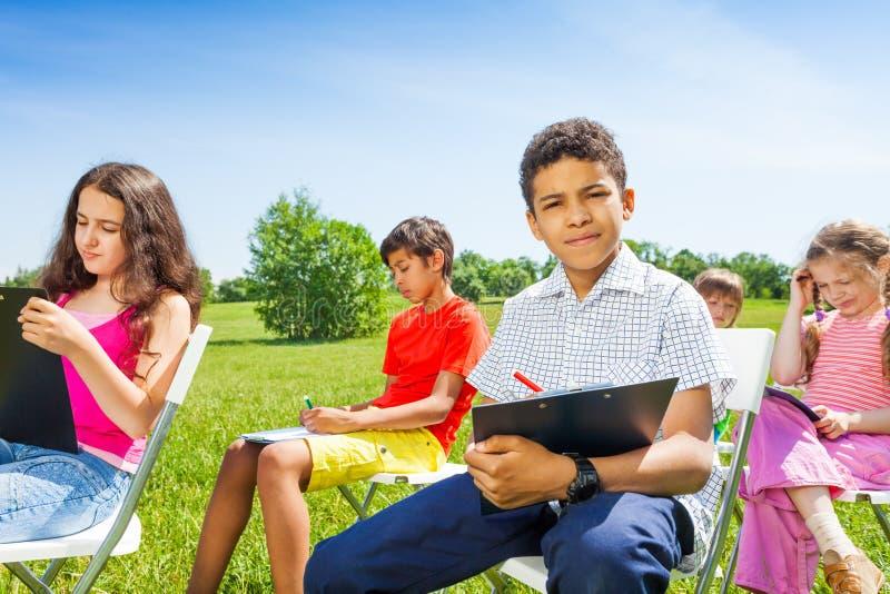 Kinderen die op klemborden samen buiten trekken stock fotografie