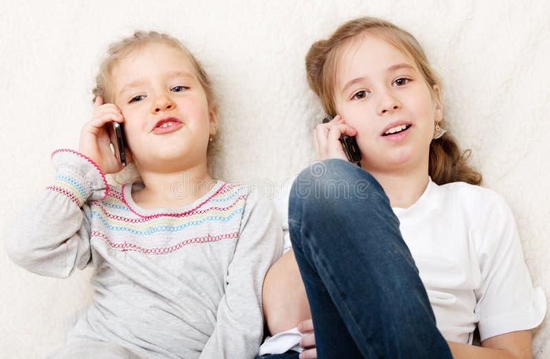 Kinderen die op mobiele telefoon spreken stock fotografie