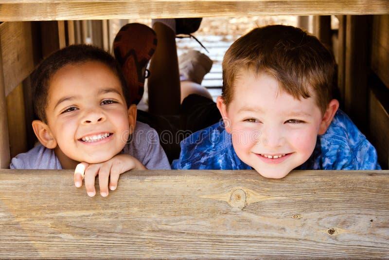 Kinderen die op speelplaats spelen stock foto