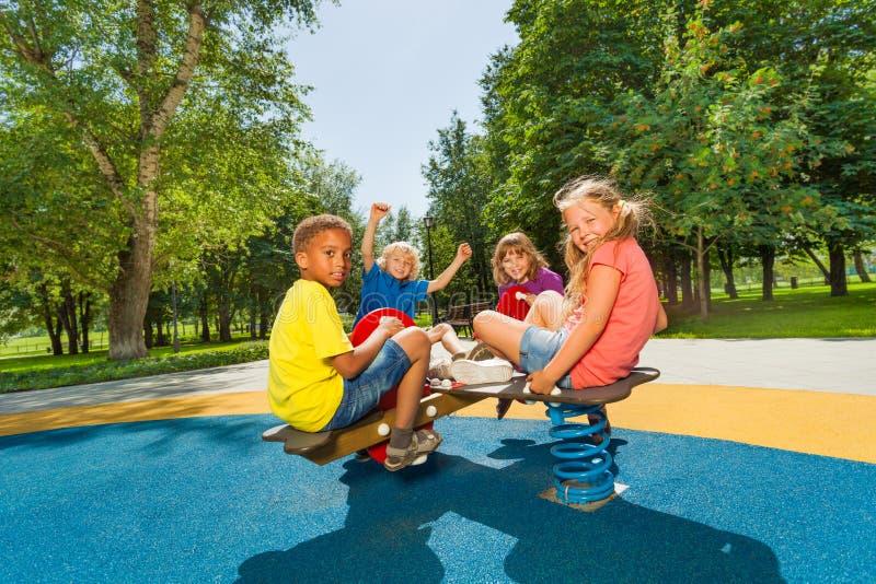Kinderen die op speelplaatscarrousel samen zitten stock afbeeldingen