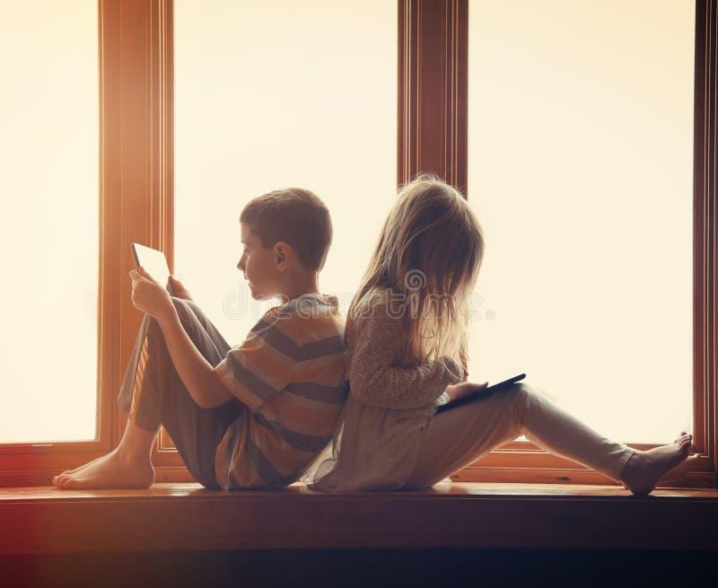 Kinderen die op Technologietabletten thuis spelen royalty-vrije stock afbeelding