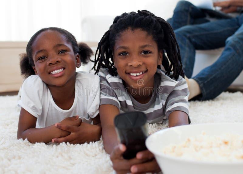 Kinderen die op televisie letten en pop graan eten stock afbeeldingen