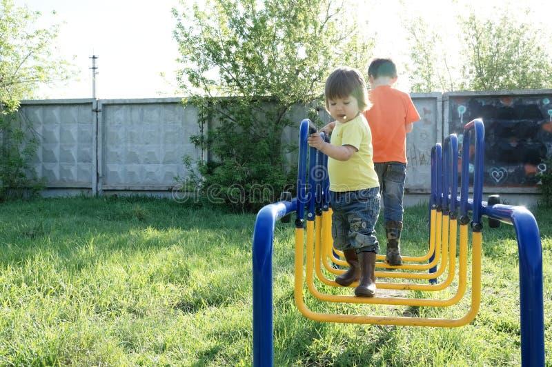 Kinderen die in openlucht spelen Jongen en meisje op speelplaats, kinderenactiviteit Actieve gezonde kinderjaren stock afbeelding