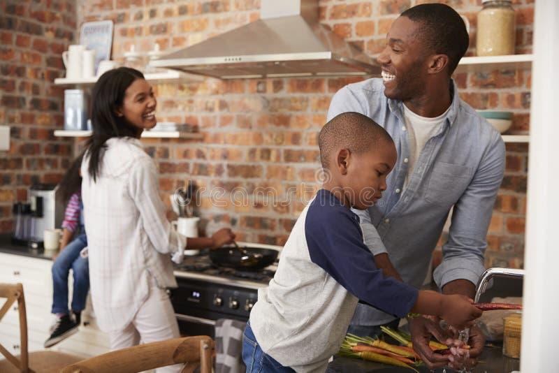 Kinderen die Ouders helpen om Maaltijd in Keuken voor te bereiden royalty-vrije stock afbeeldingen