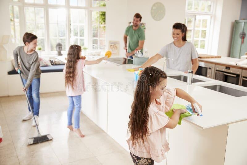 Kinderen die Ouders met Huishoudenkarweien helpen in Keuken royalty-vrije stock fotografie