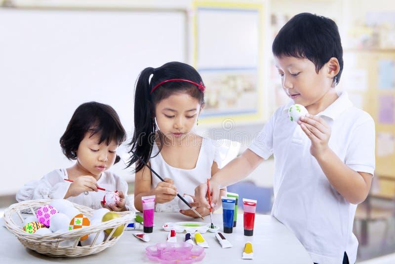 Kinderen die paaseieren in kunstklasse schilderen stock afbeeldingen