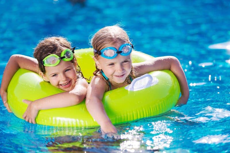 Kinderen die in Pool spelen Twee meisjes die hebben royalty-vrije stock foto