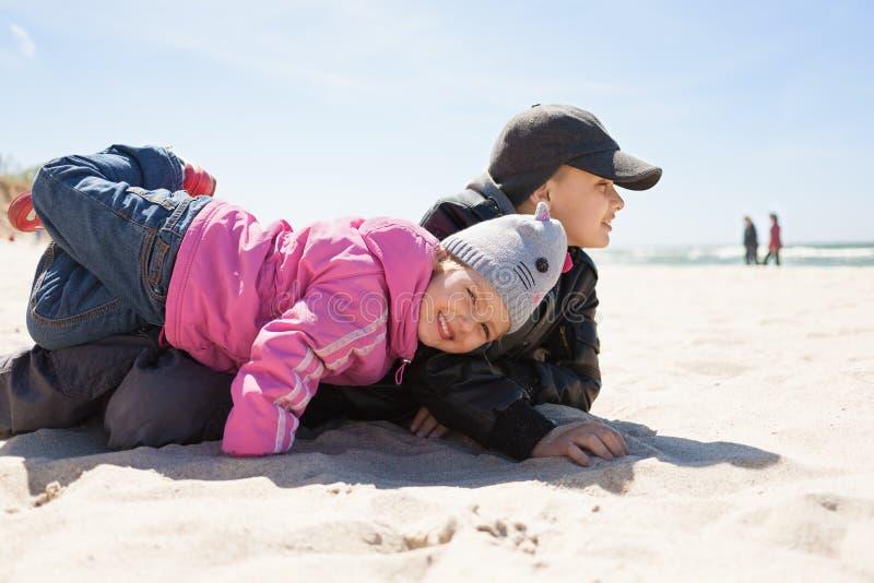 Kinderen die pret emotioneel strand spelen stock foto