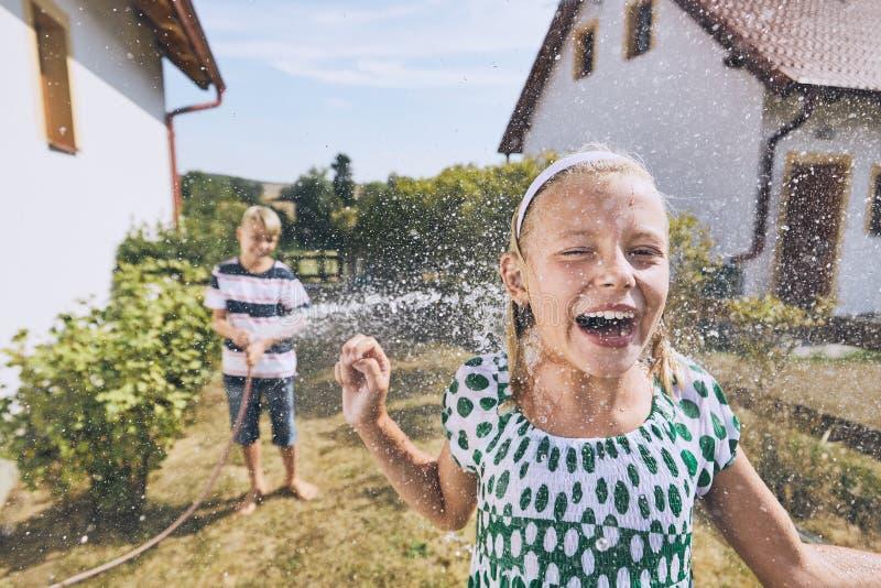 Kinderen die pret met het bespatten van water hebben stock afbeelding