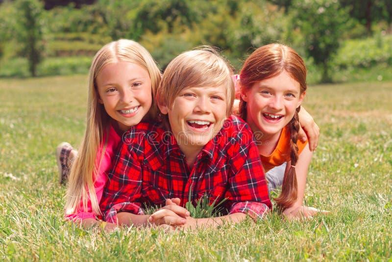 Kinderen die pret op het gras hebben stock afbeeldingen