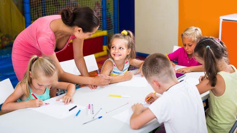 Kinderen die samen en in klasse op school trekken zitten stock foto's