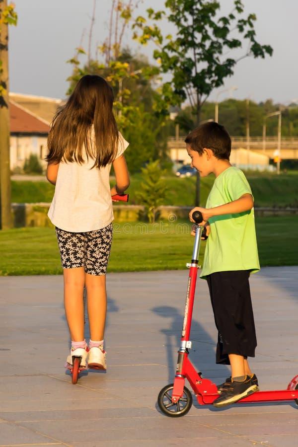 Kinderen die schopautoped in de zomerdag berijden stock fotografie