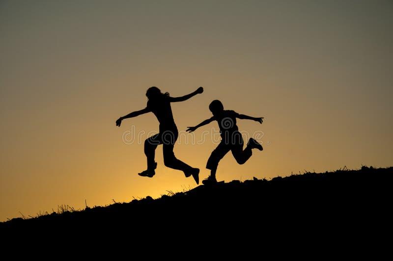 Kinderen die silhouet in werking stellen stock fotografie