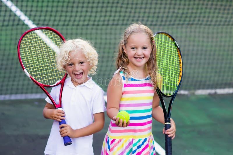 Kinderen die tennis op openluchthof spelen royalty-vrije stock foto