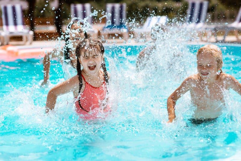 Kinderen die terwijl het bespatten van water in zwembad lachen royalty-vrije stock fotografie