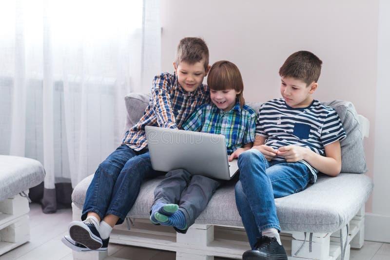 Kinderen die thuis op bank zitten, die met laptop spelen royalty-vrije stock fotografie