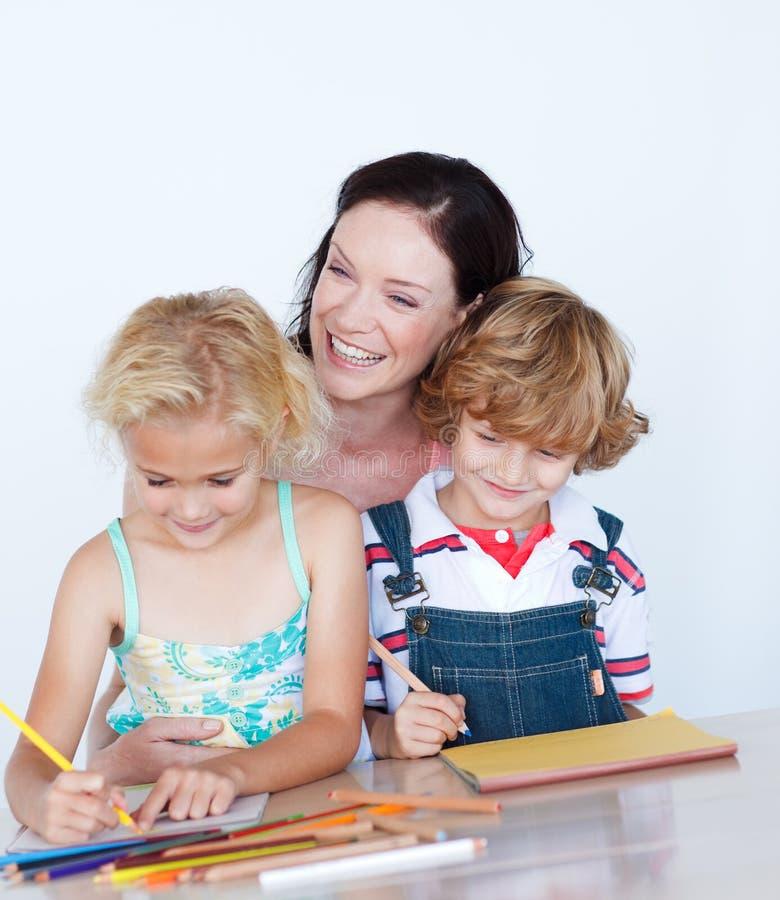 Kinderen die thuiswerk met hun moeder doen stock afbeelding