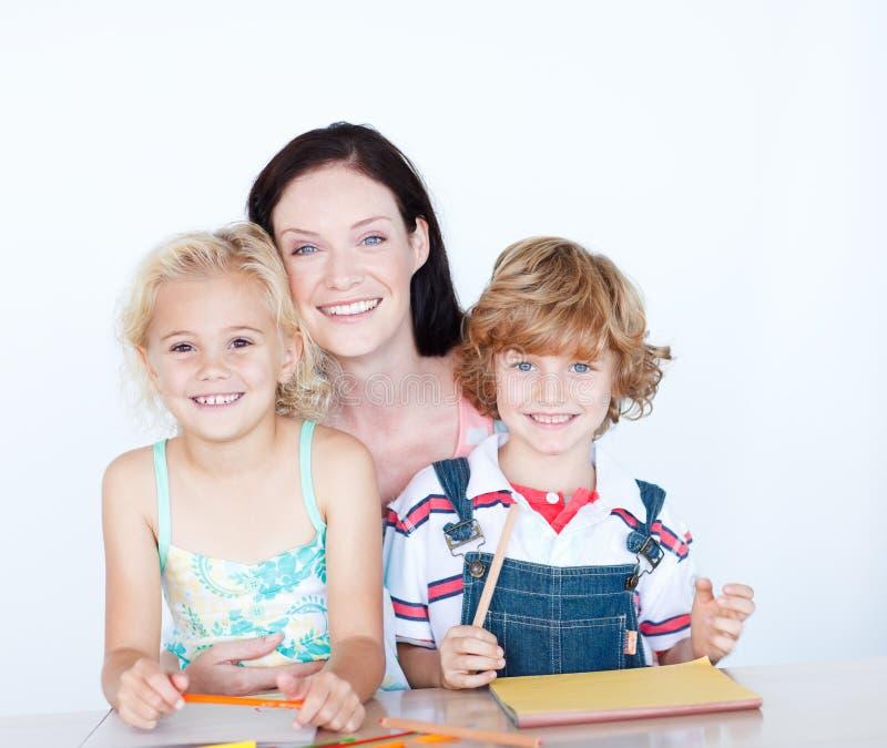 Kinderen die thuiswerk met hun moeder doen stock foto