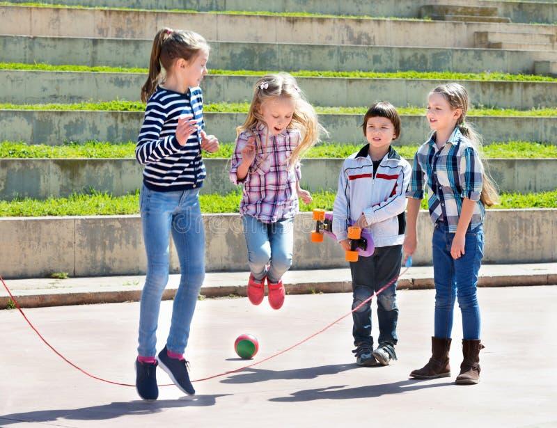 Kinderen die touwtjespringen springend spel spelen stock fotografie