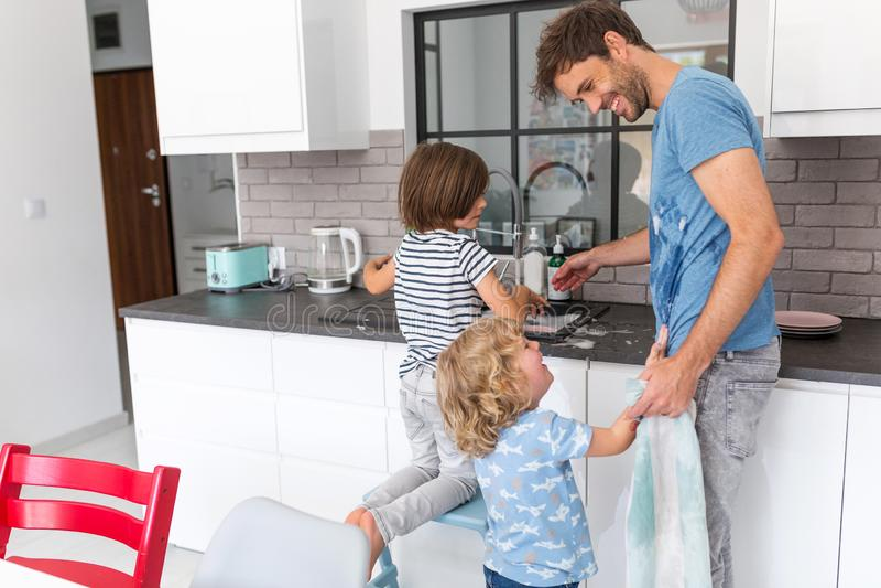 Kinderen die vader in keuken helpen stock fotografie