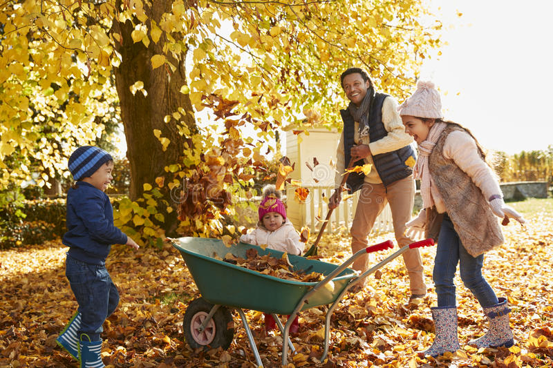 Kinderen die Vader To Collect Autumn Leaves In Garden helpen stock foto
