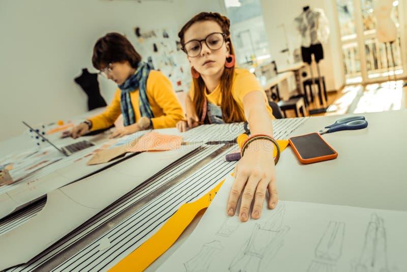 Kinderen die van manierontwerper hun schetsen van de moedertekening helpen royalty-vrije stock afbeelding