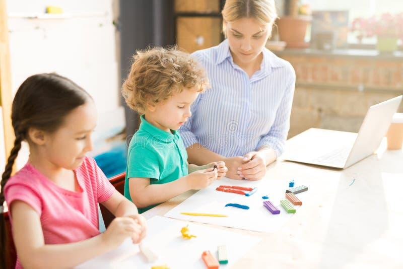 Kinderen die van spelklei beeldhouwen stock afbeelding