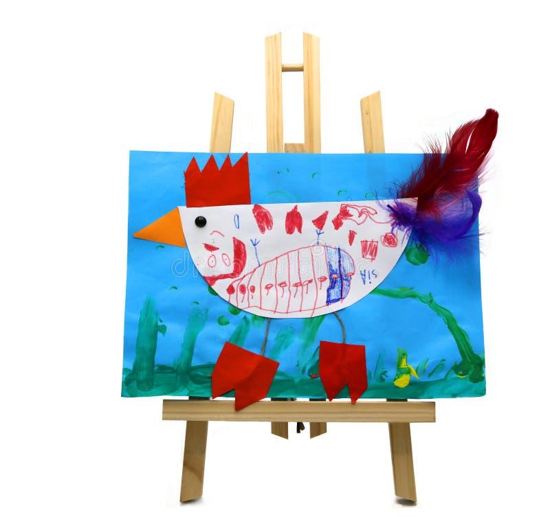 Kinderen die vertegenwoordigend een kip met gekleurde veren op blauw document trekken dat op een houten schildersezel wordt getoo royalty-vrije stock afbeelding