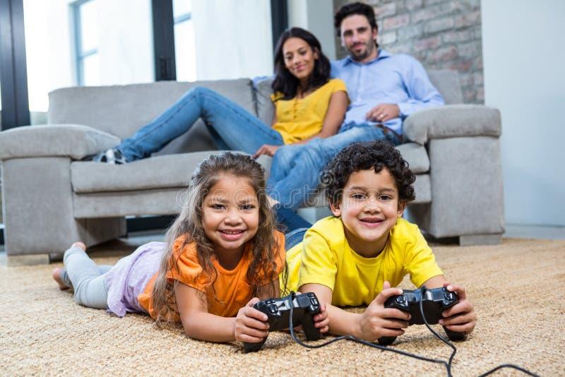 Kinderen die videospelletjes op het tapijt in woonkamer spelen royalty-vrije stock foto