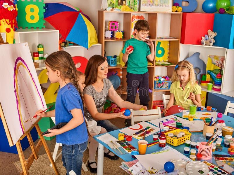 Kinderen die vinger op schildersezel schilderen Groep jonge geitjes met leraar stock afbeelding