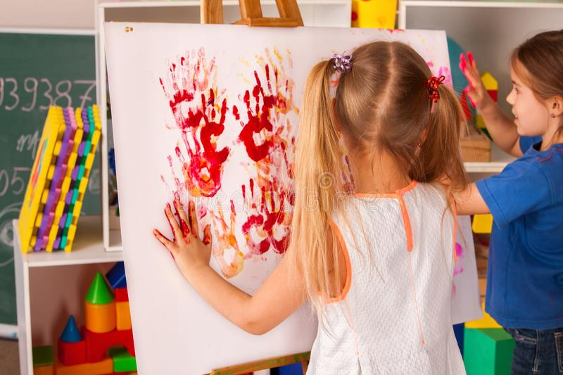 Kinderen die vinger op schildersezel schilderen Groep jonge geitjes met leraar royalty-vrije stock fotografie