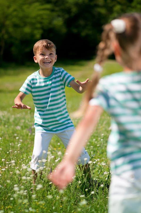 Kinderen die vliegende schijf spelen stock foto's