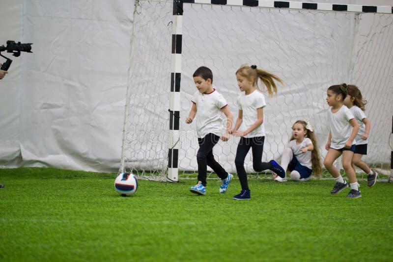 Kinderen die voetbal binnen spelen Jonge geitjes die naar de bal lopen royalty-vrije stock fotografie