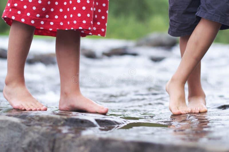 Kinderen die voeten in een beek doorweken stock afbeelding