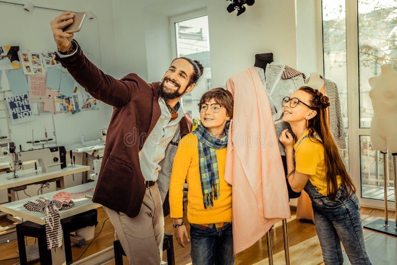 Kinderen die voor foto met hun houdende van moderne vader stellen stock foto's
