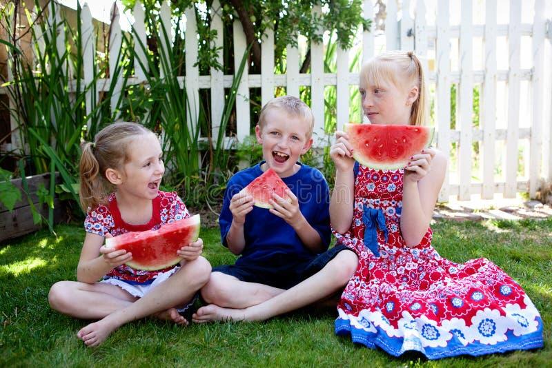 Kinderen die Watermeloen eten stock afbeelding