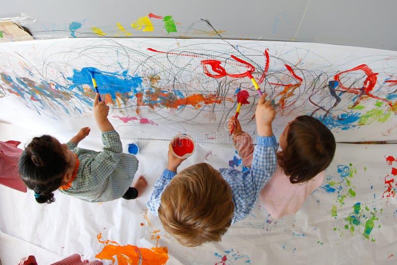 Kinderen die wijd gebruikend waterverf binnen hun klaslokaal schilderen stock afbeelding