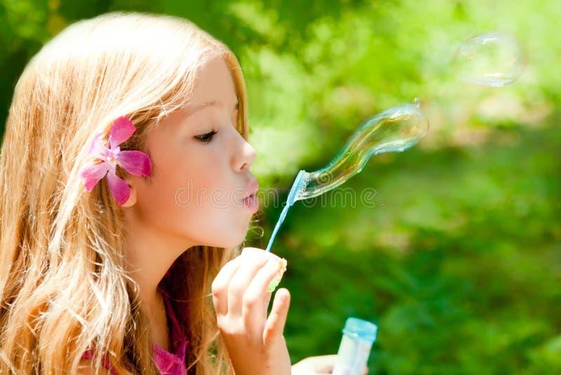 Kinderen die zeepbels in openluchtbos blazen stock foto