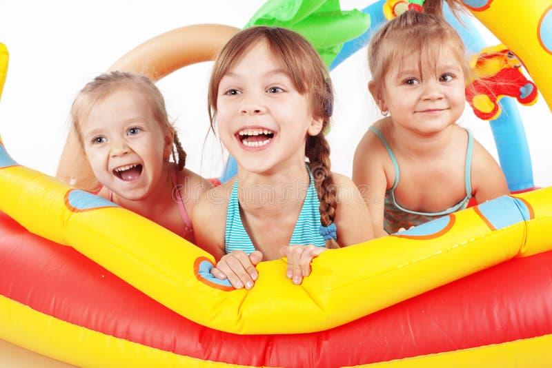 Kinderen die in zwembad spelen stock foto's