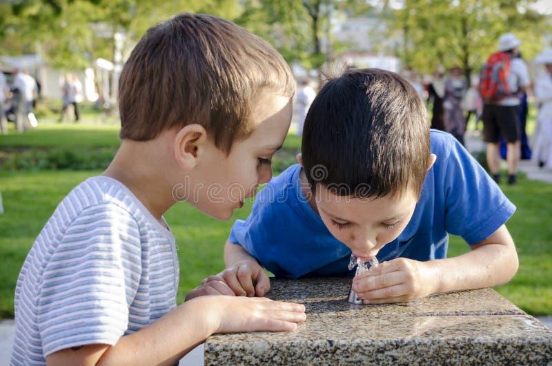 Kinderen drinkwater van fontein stock afbeelding